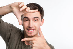 Cheerful young man is trying to photograph Stock Photos