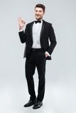 Cheerful young man in tuxedo with bowtie showing ok sign Stock Photo