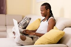 Cheerful young man typing on laptop. Side view of cheerful young black man typing on laptop while sitting on couch Stock Photo