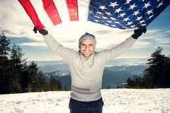 Cheerful young man with USA flag. Cheerful happy young man with a big smile holding USA flag, looking at the camera and smiling. Warmer highlights, lens flare Stock Images