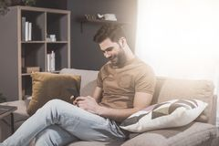 Cheerful young man is using mobile phone at home royalty free stock images
