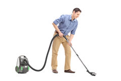 Cheerful young man using a vacuum cleaner Royalty Free Stock Photo