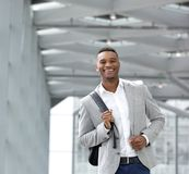 Cheerful young man walking at airport with bag Stock Photos