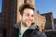 Cheerful young man walking in the city. Close up portrait of a cheerful young man walking in the city Royalty Free Stock Images