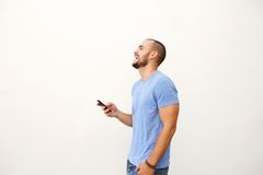 Cheerful young man walking with mobile phone Stock Photography