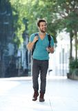Cheerful young man walking with mobile phone and bag Stock Photography
