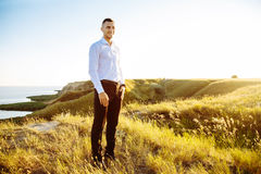 Cheerful young man in white shirt standing near the sea Royalty Free Stock Images