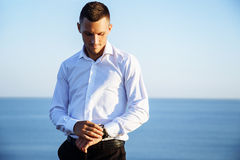 Cheerful young man in white shirt standing near the sea Royalty Free Stock Photography