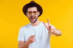 Cheerful young man in white t-shirt, hat and sunglasses showing victory sign and pointing with finger. Isolated on yellow Royalty Free Stock Photography