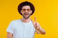 Cheerful young man in white t-shirt, hat and sunglasses showing victory sign and smiling at camera. Isolated on yellow Stock Images