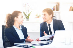 Cheerful young man and woman coworkers talking in firm office Stock Image