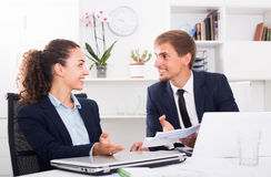 Cheerful young man and woman coworkers talking in firm office Royalty Free Stock Image