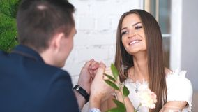 Cheerful young man and woman are dating in restaurant. They are sitting at the table and looking at each other with love. The lovers are drinking wine and stock video footage