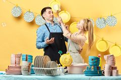 Cheerful young man and woman having foam party in the kitchen. stock photo