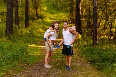 A cheerful young man and woman are holding two children on their backs in the summer outdoors. family. A cheerful young men and women are holding two children on royalty free stock photography