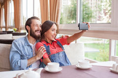 Cheerful young man and woman are making selfie in Stock Image
