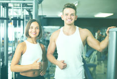 Cheerful young man and woman taking pause between exercising in Royalty Free Stock Images