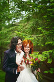 Cheerful young married couple. Happy young married couple, smiling and standing near green trees. Red hair bride. Summer evening wedding Stock Images