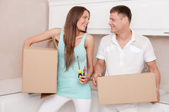 Cheerful young married couple is preparing to move Stock Photos