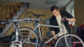 Cheerful young mechanic is doing professional bike maintenance checking tire, front wheel and frame, tightening joints. Cheerful young mechanic is doing stock video