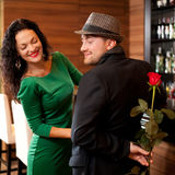 Man surprising girlfriend with flower Royalty Free Stock Photography