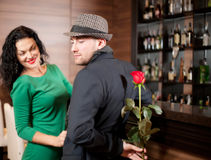 Man surprising girlfriend with flower Stock Images
