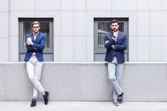 Cheerful young men are making serious decision. Handsome two businessmen are making break outdoors. They are standing on balcony and looking at camera pensively Royalty Free Stock Image