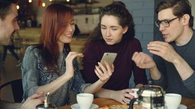 Cheerful young men and women close friends are using smartphone and talking while having lunch in nice cafe. Dining. Cheerful young men and women close friends stock footage