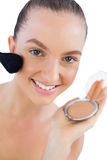 Cheerful young model applying face powder Stock Photography