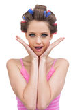 Cheerful young model with hair curlers Royalty Free Stock Photos