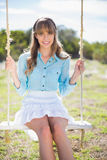 Cheerful young model posing while sitting on swing Royalty Free Stock Photo