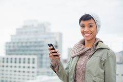 Cheerful young model in winter clothes holding her mobile phone Royalty Free Stock Image