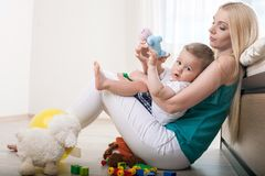 Cheerful young mom is embracing her little child Royalty Free Stock Photos