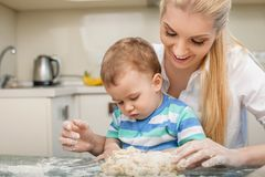 Cheerful young mom and her small son are baking. Beautiful mother and her little toddler are doing dough with fun. The women is looking at her child with love Stock Photo