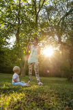 Cheerful young mother blowing soap bubbles towards  her baby boy Royalty Free Stock Photos