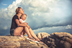 Cheerful young mother embrace her baby sitting on rocks with dramatic sky and clouds on background during sunset with copy space royalty free stock photos