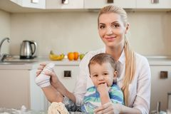 Cheerful young mother and her child in kitchen. Beautiful mom is holding her son on her knees. They are preparing dough for cookies. The boy is raising his leg Stock Photo