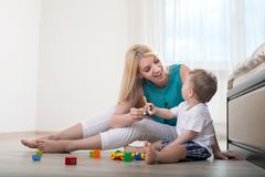 Cheerful young mother is playing with her son Stock Photos