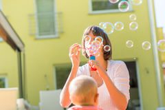 Cheerful young mother standing outdoors blowing bubbles for her Stock Photos