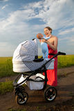 Cheerful young mother taking her baby out of pram. Cheerful young mother taking her baby boy out of the pram Stock Photography