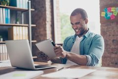 Cheerful young mulatto worker is plying a game on his tablet in office. He is very excited, wearing casual smart, funny grimace. Happy funny funky guy Stock Images