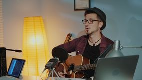 Cheerful young musician playing the guitar and singing into microphone in home studio stock video footage