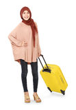 Cheerful young muslim woman carrying a suitcase Royalty Free Stock Photography