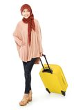 Cheerful young muslim woman carrying a suitcase. Isolated on white background Royalty Free Stock Photos