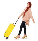 Cheerful young muslim woman carrying a suitcase. Isolated on white background Stock Images