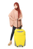 Cheerful young muslim woman carrying a suitcase. Isolated on white background Royalty Free Stock Image