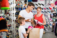 Cheerful young parents with boy in school age shopping shoes Royalty Free Stock Photo