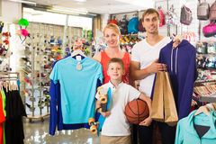 Cheerful young parents with boy in sport store. Cheerful young parents with boy in school age shopping clothing in sport store Royalty Free Stock Photo