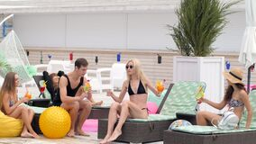 Cheerful young people in bathing suits enjoy colored drinks and sitting on sun lounger stock video