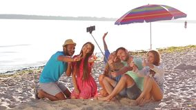 Cheerful young people doing selfie on the beach. stock footage